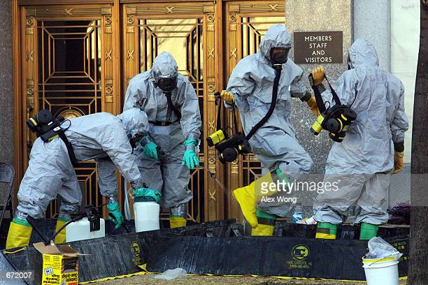 A hazardous material worker sprays his colleagues after they came out from an anthrax search at Dirksen Senate Office Building November 18 2001 on...