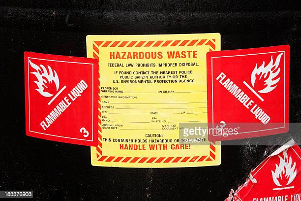 hazardous waste lables on a barrel of chemicals - flammable stock photos and pictures