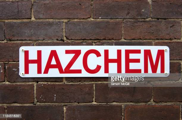 'Hazchem' hazardous chemical warning sign on a brick wall