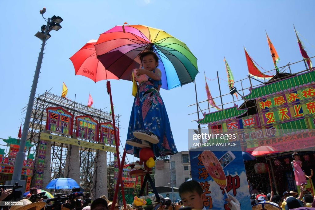 TOPSHOT - Hazel Kwok (C), 4 years old, stands on a float while portraying her character of former lawmaker Emily Lau during the annual Cheung Chau bun festival parade in Hong Kong on May 22, 2018.