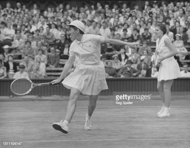Hazel Redick-Smith of South Africa playing a backhand return watched by compatriot doubles partner Dora Kilian during their Women's Doubles Third...