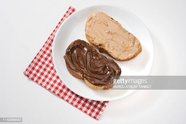 hazelnut and chocolate spread on bread - nutella stock pictures, royalty-free photos & images