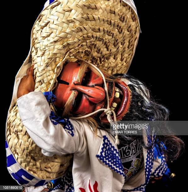 Haziel Emmanuel Hernandez Martinez poses for a photograph with his traditional costume during the presentation of the Huey Atlixcayotl Festival on...