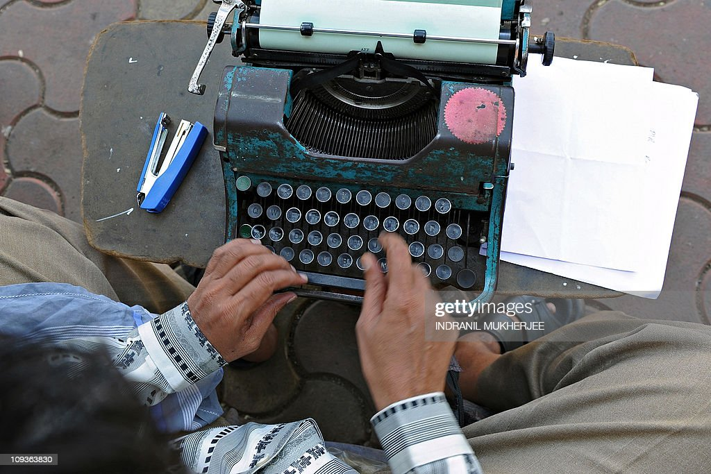 HAZLEWOODThis photo taken on February 15, 2011 shows professional typist Purushottam Sakhare typing an affidavit on his typewriter at a sidewalk outside a city court in Mumbai. Typewriters have largely been consigned to history in many countries and might be expected to have also been sent for scrap in Mumbai, where India does business with the world and the latest technology drives the country's economic boom. But the unmistakeable clatter of typewriter keys and sound of tinny margin bells can still be heard, echoing down the vaulted corridors of the courts and lawyers' chambers to police stations and government offices across the city. AFP PHOTO/ Indranil MUKHERJEE