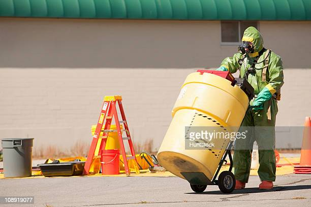 hazmat firefighter pushing a salvage drum - hazmat stock pictures, royalty-free photos & images