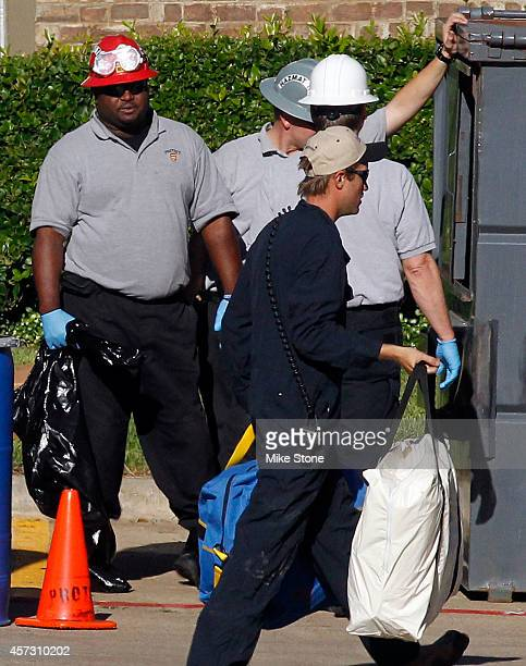 A hazmat worker carries bags containing protective suites inside of The Village Bend East apartment complex where a second health care worker who has...
