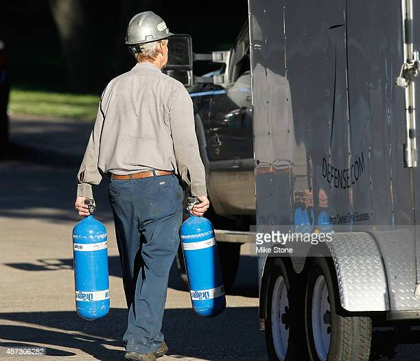 A hazmat worker carries two tanks from a hazmat semitrailer at the The Village Bend East apartment complex where a second health care worker who has...