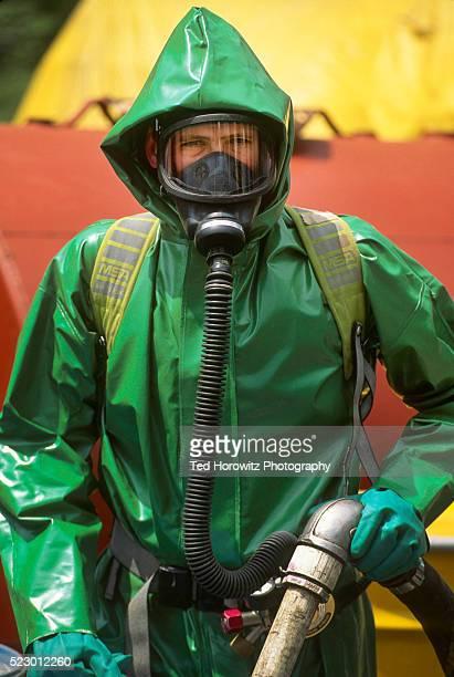 Hazmat worker in green protective suit.
