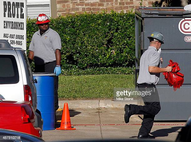 A hazmat worker jogs towards the aparment in The Village Bend East complex where a second health care worker who has tested positive for the Ebola...
