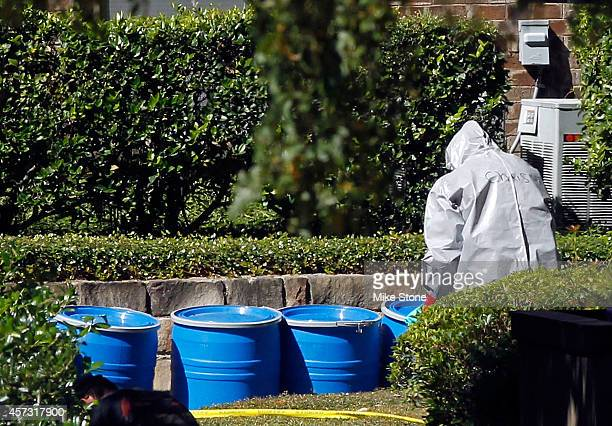 A hazmat worker moves a barrel of waste material from The Village Bend East apartment where a second healthcare worker who has tested positive for...
