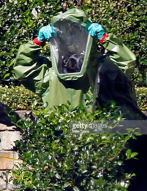 A hazmat worker puts on protective clothing before entering The Village Bend East apartment complex where a second healthcare worker who has tested...