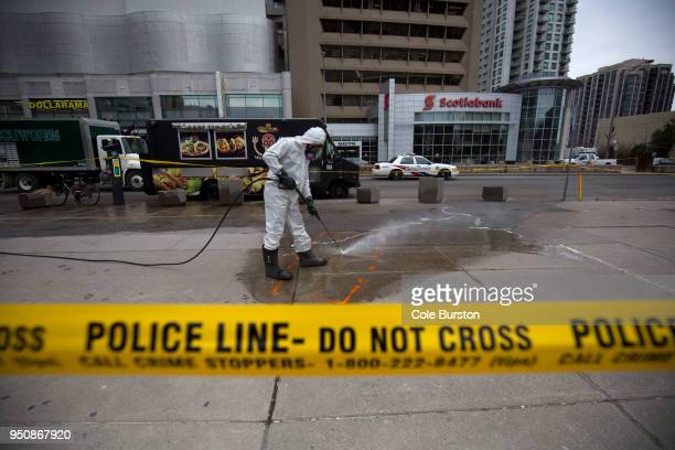 A hazmat worker scrubs the sidewalk of blood and debris in an outline of where a body laid after a mass killing on Yonge St at Finch Ave on April 24...