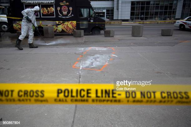 A hazmat worker scrubs the sidewalk of blood and debris near an outline of where a body laid after a mass killing on Yonge St at Finch Ave on April...