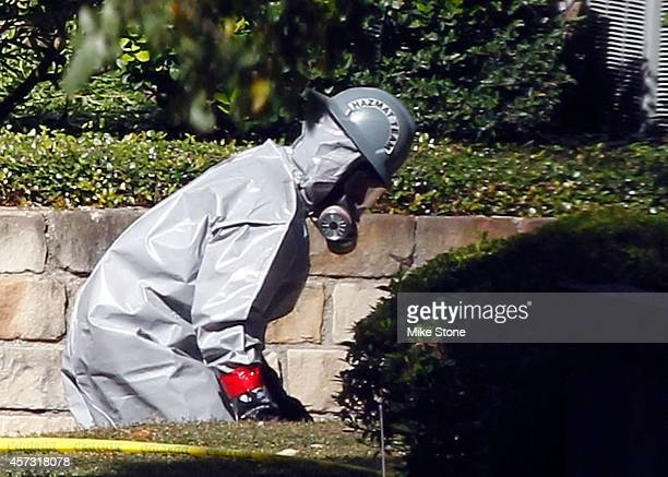 A hazmat worker stumbles as he walks towards The Village Bend East apartment where a second healthcare worker who has tested positive for the Ebola...