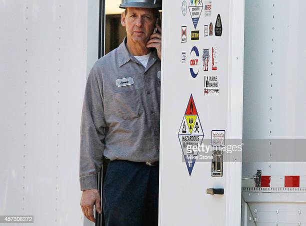 A hazmat worker talks on the phone inside of a hazmat semitrailer at the The Village Bend East apartment complex where a second health care worker...