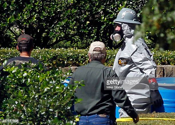 A hazmat worker walks past a row of barrels removed from The Village Bend East apartment where a second healthcare worker who has tested positive for...