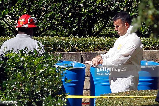 A hazmat worker washes his hands after coming out of The Village Bend East apartment where a second healthcare worker who has tested positive for the...