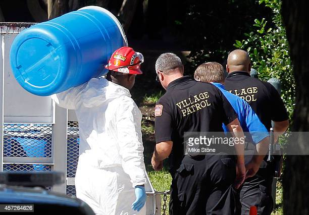 A hazmat worker with Protect Environmental carries a barrel in preparation for decontaminating an apartment as security personnel are near at The...