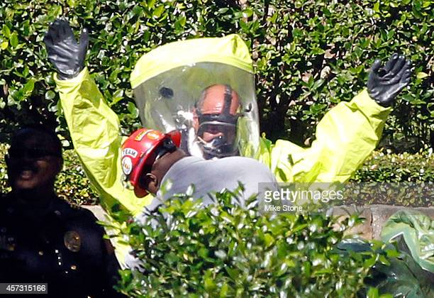 Hazmat workers help each other put on protective clothing before entering The Village Bend East apartment complex where a second health care worker...