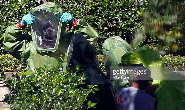 Hazmat workers put on protective clothing before entering The Village Bend East apartment complex where a second healthcare worker who has tested...