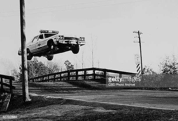 Hazzard County police car jumps over a small bridge in a still from the CBS action comedy series 'The Dukes of Hazzard,' December 14, 1978. The first...