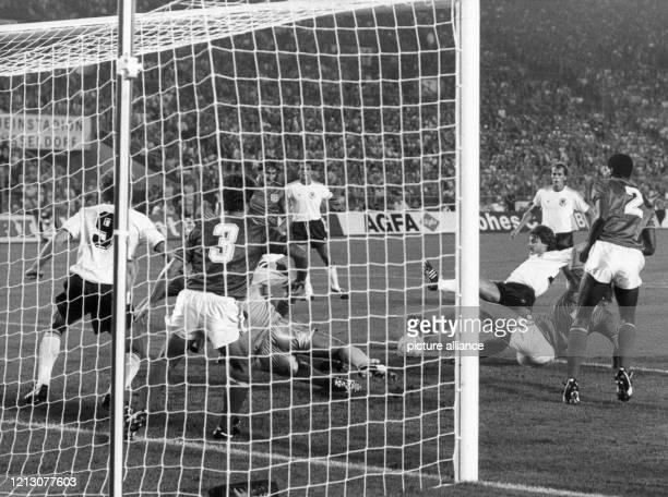 Der deutsche Mittelfeldspieler Olaf Thon versucht im Fallen auf das Tor zu schießen Sein Teamgefährte Rudi Völler steht auf der englischen Torlinie...