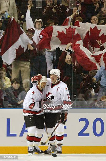 Team Canada's Steve Yzerman is congratulated by teammate Mario Lemieux as Canadian fans celebrate in background during second period semi final...