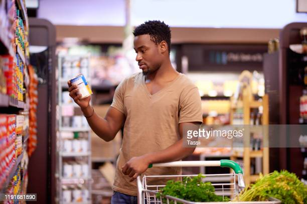 he always reads the labels to make more informed decisions - man shopping stock pictures, royalty-free photos & images