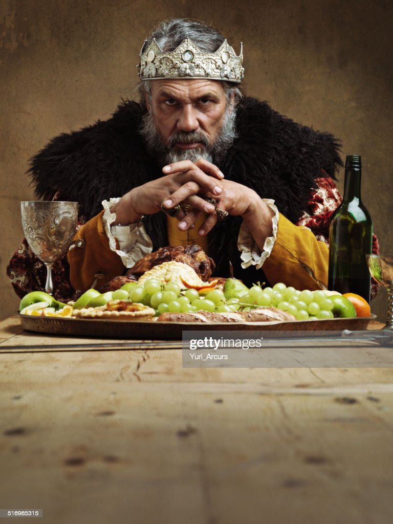 He feasts while the serfs starve : Stockfoto