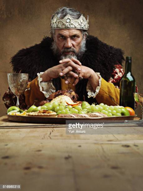 he feasts while the serfs starve - king royal person stock photos and pictures