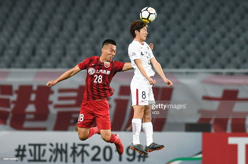 He Guan #28 of Shanghai SIPG and Shoma Doi #8 of Kashima Antlers compete for the ball during the AFC Champions League Round of 16 second leg match between Shanghai SIPG and Kashima Antlers at Shanghai Stadium on May 16, 2018 in Shanghai, China.