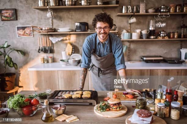 egli è nel suo elemento durante la cottura - chef foto e immagini stock