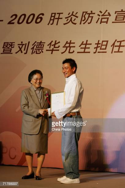 He Luli Director of Chinese Foundation For Hepatitis Prevention And Control presents an ambassador certificate to Hong Kong star Andy Lau during a...