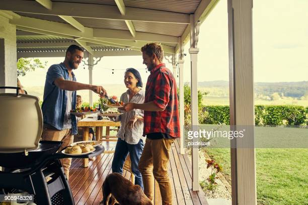 he sure knows how to host a lunch - barbecue social gathering stock pictures, royalty-free photos & images