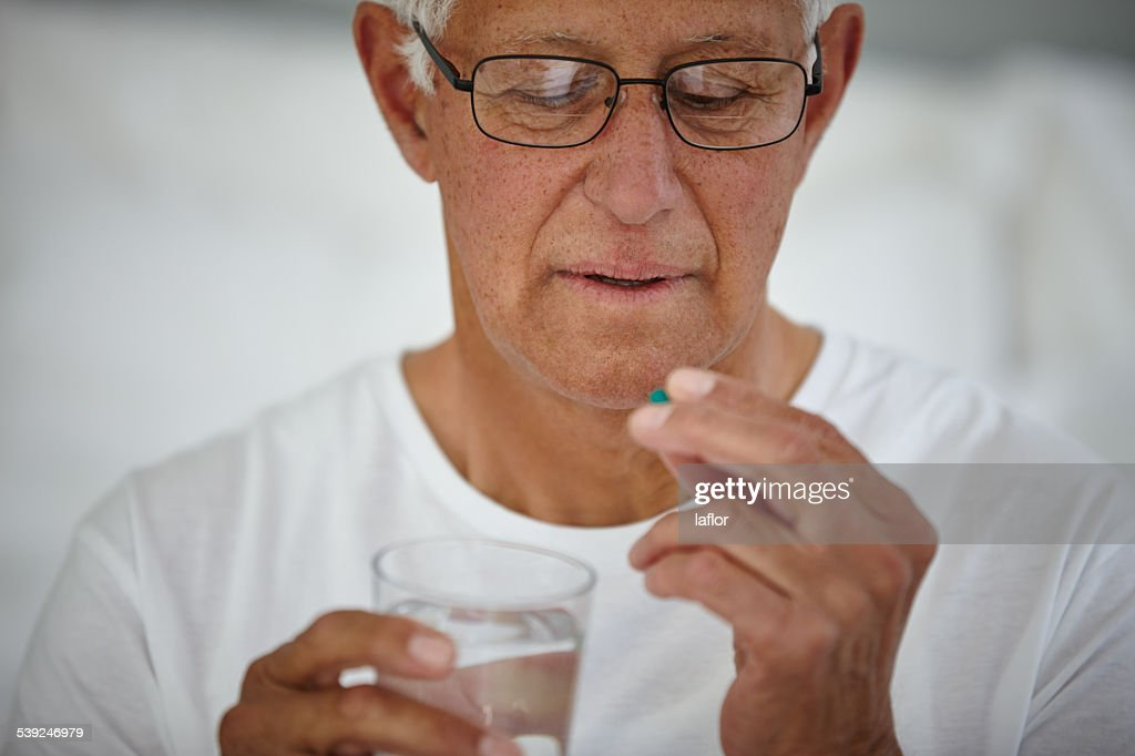 He takes his medicine first thing in the morning : Stock Photo