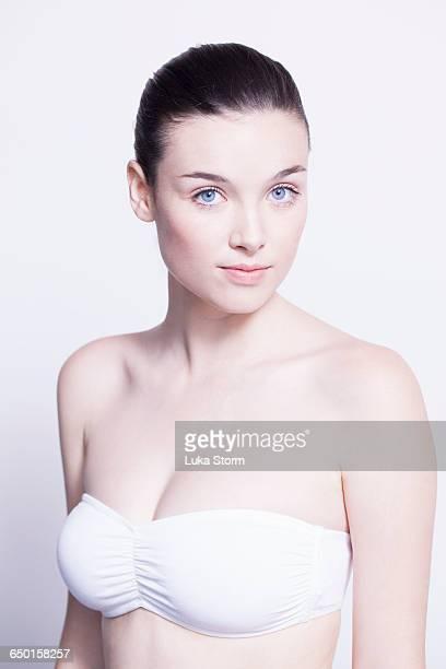 Head and shoulder portrait of beautiful young woman wearing white bikini top