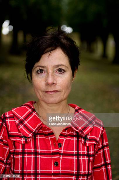 head and shoulder portrait of danish woman, 53 years old, in red, plaid coat at frederiksberg park, copenhagen, denmark - 50-59 years and women only fotografías e imágenes de stock