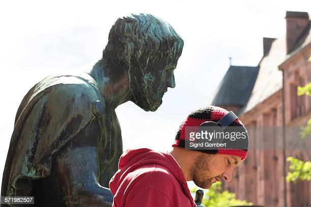 head and shoulder portrait of mid adult man wearing headphones in front of sculpture, freiburg, baden, germany - sigrid gombert stock pictures, royalty-free photos & images