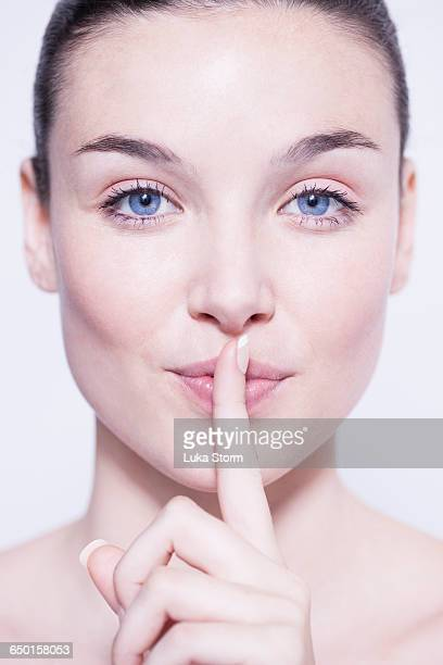 Head and shoulder shot of beautiful young woman with finger on lips