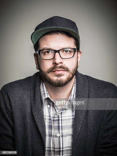 Head and shoulder studio portrait of bearded young man wearing spectacles and baseball cap