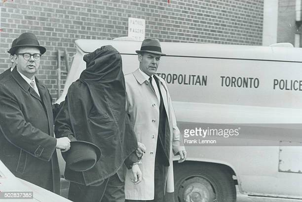 Head and shoulders covered to prevent identification George Ronald Waite father of four charged with seven bank holdups in Metro leaves police...