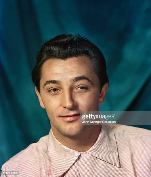 Head and shoulders of a young Robert Mitchum He is smiling and wearing a white shirt Undated color slide