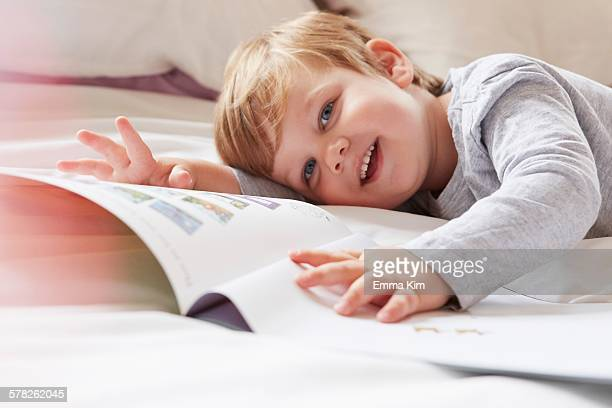 Head and shoulders of boy on bed lying on front holding storybook, looking away smiling