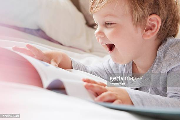 Head and shoulders of boy on bed lying on front looking at storybook, laughing