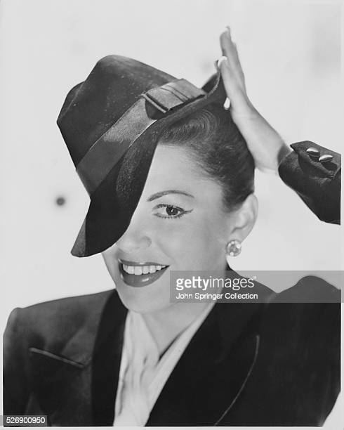 Head and shoulders of Judy Garland with her hat tipped to the side covering the top corner of her face Ca 1950s