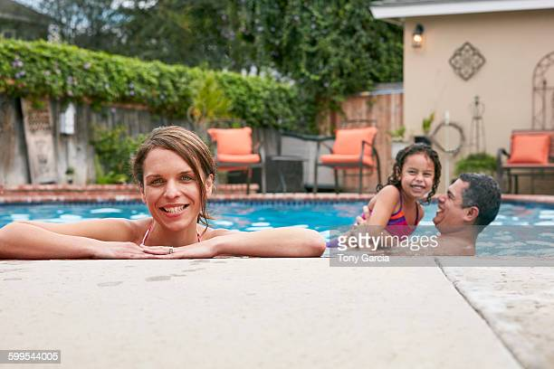 Head and shoulders of mid adult woman with family in pool looking at camera smiling