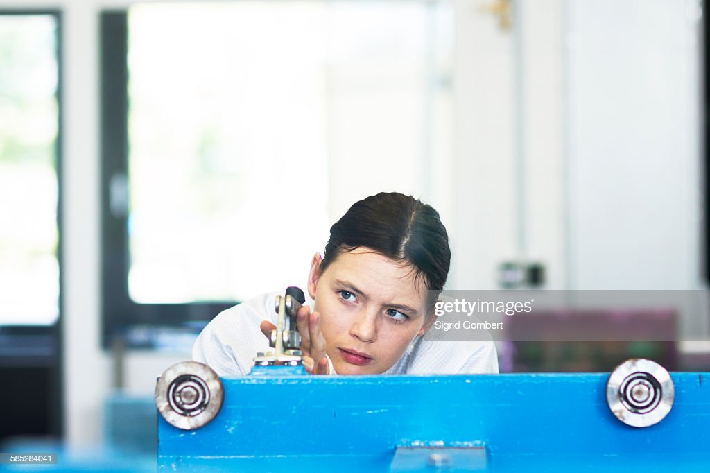 Head and shoulders of young woman operating machine : Stock-Foto