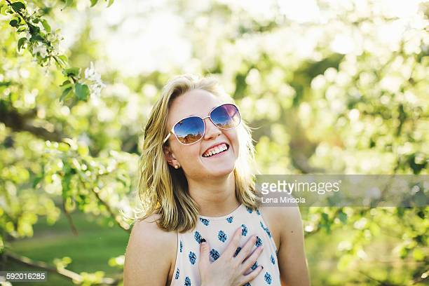 Head and shoulders of young woman wearing sunglasses, hand on chest looking at camera laughing