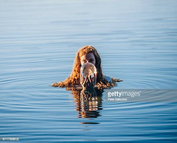 head and shoulders of young woman with long red hair in lake holding crystal ball - lake auburn stock photos and pictures