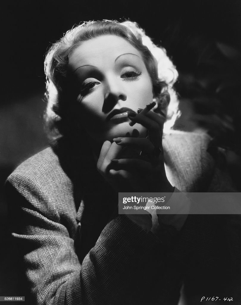 head and shoulders photo of actress marlene Dietrich (1901-92) smoking a cigarette.
